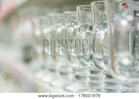 Closeup of emplty glasses with handle standing on shelf in supermarket