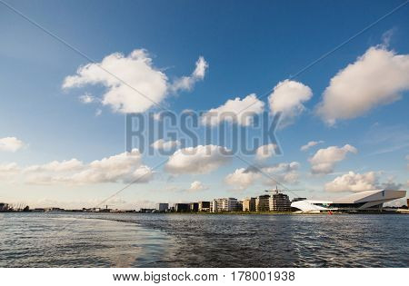 Spring sunny Amsterdam. The bright clear blue sky with white clouds. Boat trip on the canals of Amsterdam. The bridge over the water. Travel to Europe