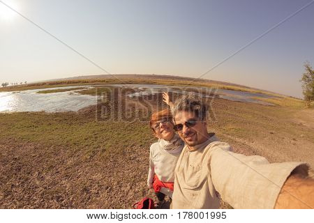 Couple taking selfie on Chobe River Namibia Botswana border Africa. Fisheye view from above toned image. Chobe National Park famous wildlilfe reserve and upscale travel destination.