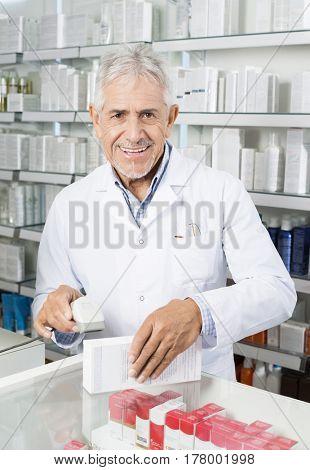 Portrait Of Chemist Scanning Barcode On Medicine Box