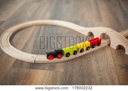 Wooden toy train on railroad with wooden bridge. Clean laminated floor