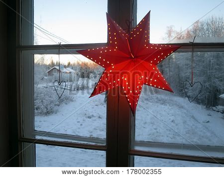 A christmas star in the window - outside is snowy.