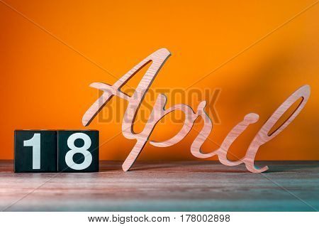 April 18st. Day 18 of month, daily wooden calendar on table with orange background. Spring time concept.