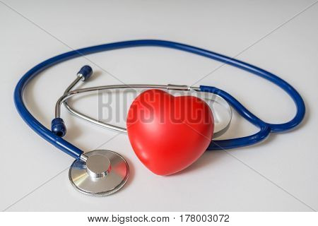 Red Plastic Heart And Stethoscope On White Background.