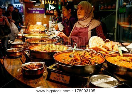 LONDON, UK - APRIL 10, 2016: Traders at a market stall selling curry and variety of cooked foods at Camden Market, London.