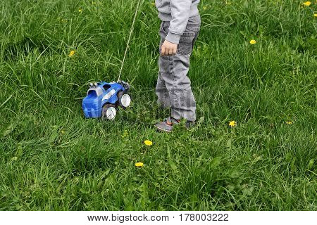 The image of a child dressed in gray pants and a sweatshirt. The child playing among the thick green grass on the street. Boy playing with toy car: the car carries the rope.