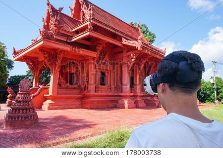Man in Virtual Reality Glasses Looking at Buddhist Temple in Thailand