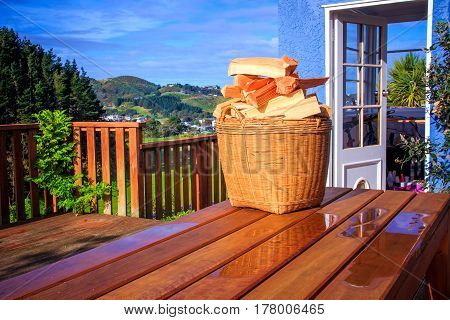 sunny landscape, basket with chopped firewood in the basket at the table photo - alternative energy
