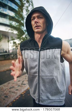 Athletic man with serious face in sleeveless hoodie training jogging outside in the city on cloudy day close-up front portrait