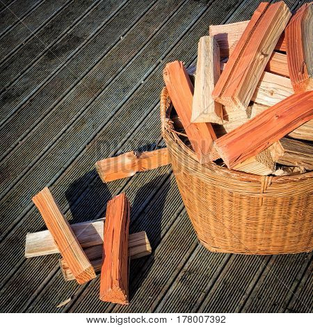 chopped firewood stack at the basket at the wooden floor photo