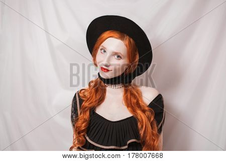 A woman with a smirk with long red straight hair in a black hat on a white background. Red-haired girl with pale skin blue eyes a bright unusual appearance in a black dress