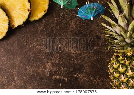 Tropical fruit. concept. Ripe tropical pineapple and cocktail umbrellas on a dark table with a marble texture with scratches. Cut fruit. Healthy eating. Going on a journey to the south. Tropical fruit. Delicious tropical food. Background with tropical fru
