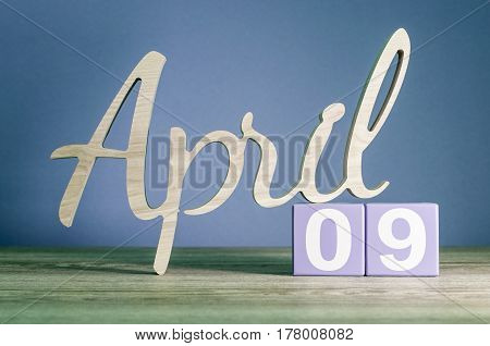 April 9th. Day 9 of month, daily calendar on wooden table with purple or violet background. Spring time theme.
