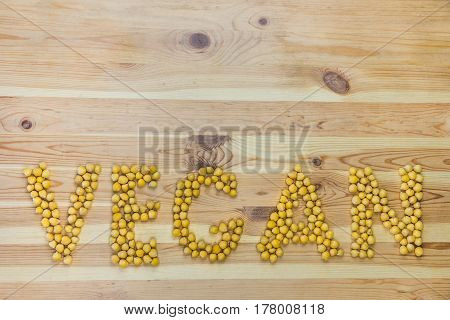 Word Vegan made of chickpeas. Gram chickling peas lay out on wood table in the shape of letters that form vegan word