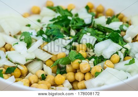 Cheakpeas, onions and leaves of parsley. Close-up image of cooked chickpeas, chopped onion, garlic and fresh parsley in bowl
