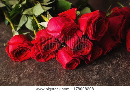 Roses lie on a dark marble table. Big beautiful bouquet of red roses. Texture roses colors. A gift for a wedding birthday Valentine's Day. Space for text and design with roses. Flat lay roses copyspace.
