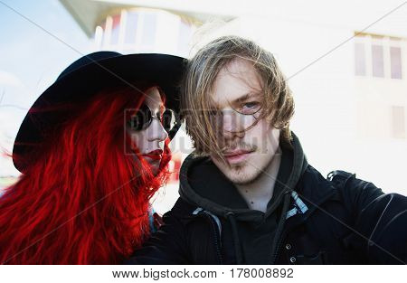 Selfie picture concept. Selfie on the nature. Selfie on camera. Selfie photo of man and woman with red curly hair in blue coat on background big city. Red-haired girl with pale skin and bright appearance with black hat on head. Street style. Make selfie