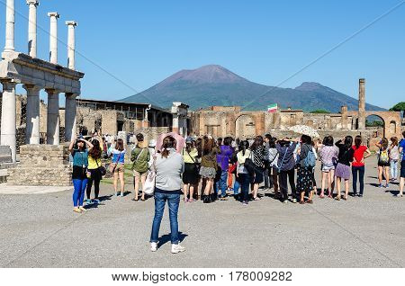 Pompeii, Italy 03 october 2013: tourists in the ancient Roman forum of the archaeological site of Pompeii with Vesuvius in the background. Naples Italy