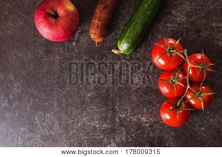Vegetables for salad. Red tomatoes apple carrot green cucumber lying on a dark marble table. Space for text and design. Flat lay vegetables copyspace. Vegetables lie on the table. Healthy vegetables. Fresh vegetables on a dark background.