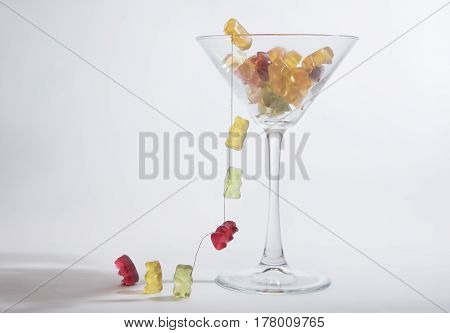 Gummy bears escaping from a clear glass