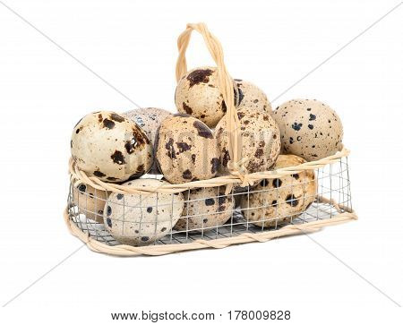 Raw quail eggs in an iron basket on a white background