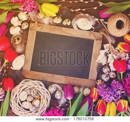 Spring easter frame with fresh flowers, eggs and rabbits on textured wooden table with copy space on empty blackboard, retro toned