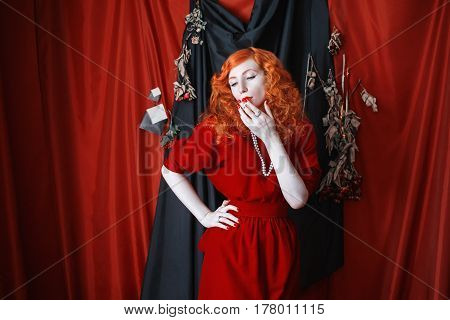 A fetish woman with red hair in a red fitting dress with a cigarette in her mouth. Red-haired fetish girl with pale skin and blue eyes with a bright unusual appearance with beads around her neck. Noir image. Fetish model
