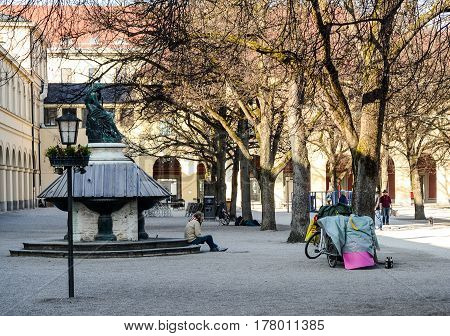 Munich,Germany-March 23,2017: A homeless man sits by a boarded fountain with his belonging packed on a bicycle nearby
