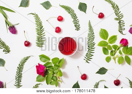 Red tea in a cup green blades of grass with purple flowers leaves birch twigs rose with red flowers green ferns ripe cherries lie on a white background. Flat lay tea top view. Herbal tea. Time is tea. Tea in a white cup. Concept with red tea. Drinking del