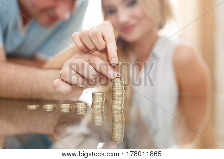 Young couple building money column from coins at home