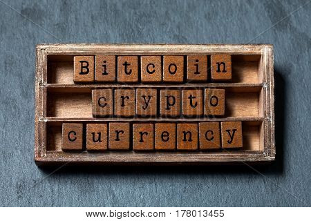 Bitcoin crypto currency and digital money concept. Vintage box, wooden cubes phrase with old style letters. Gray stone textured background. Close-up, up view, soft focus