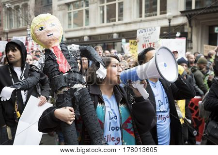 45th Presidential Inauguration, Donald Trump: A woman holding a Trump pinata effigy shouts into a megaphone to protest against immigration near a security checkpoint, WASHINGTON DC - JAN 20 2017
