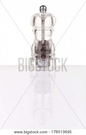 Pepper grinder made of glass isolated on white, with reflection