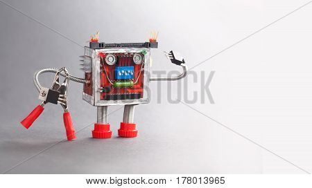 Electrician robot ready for work. Serviceman toy character with red pliers. Gray background photo.