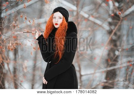 Model smoke. A woman smoke with red hair in a black coat on background of a winter forest with a mouthpiece in hand. Red-haired girl smoke with bright appearance with a turban on her head with a cigarette. Smoke aesthetics