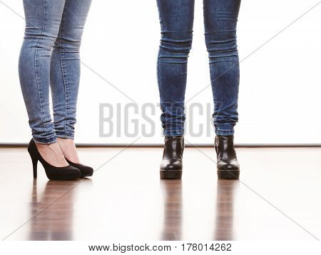 Fashion outfit. Female legs in denim pants and black high heels shoes