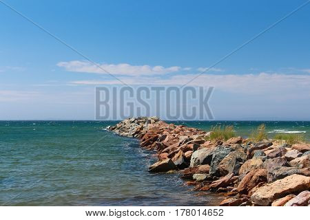 Rock pier in Magdalen Island with blue sky white clouds and calm bleu sea