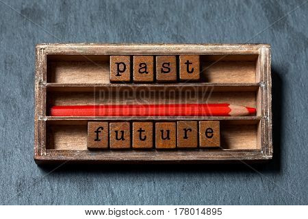 Past future concept. Vintage box, wooden cubes phrase with old style letters, old red pencil. Gray stone textured background. Close-up, up view, soft focus