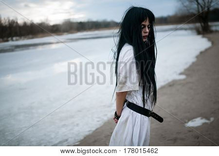 Crazy Young Woman Stands On Sand Along Lake. Side View.