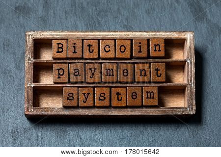 Bitcoin payment system concept. Vintage box, wooden cubes phrase with old style letters. Gray stone textured background. Close-up, up view, soft focus