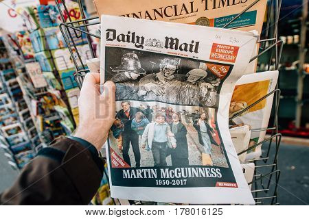 PARIS FRANCE - MAR 23 2017: Man purchases Daily Mail newspaper from press kiosk newsstand featuring James Martin Pacelli McGuinness tribute. He was an Irish republican and Sinn Féin politician who was the deputy First Minister of Northern Ireland