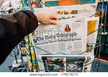 PARIS FRANCE - MAR 23 2017: Man purchases The Daily Telegraph with title New Terror ban of iPad - newspaper from press kiosk newsstand featuring headlines