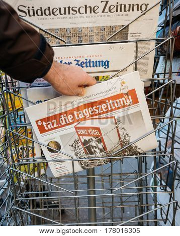 PARIS FRANCE - MAR 23 2017: Man purchases Die Tageszeitung newspaper from press kiosk newsstand featuring headlines with Deniz Yucel imprisoned under the charge of espionag by Turkish Police