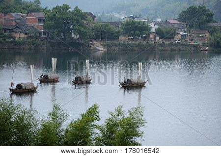 Chinese fishing boats on the river with a village on the background