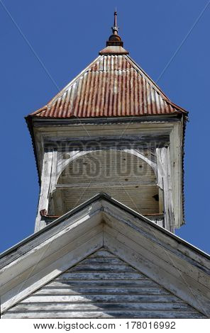 old abandoned wooden white church steeple with rusted tin roof