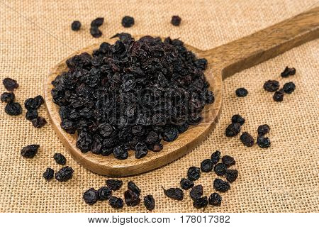 Black raisins in wooden spoon on sackcloth