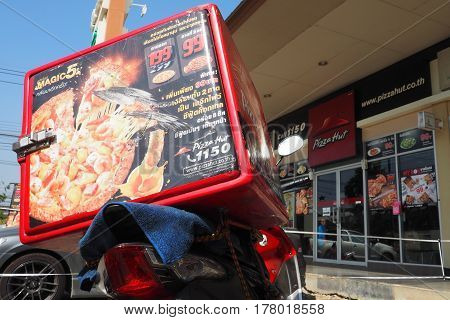 Photo focus select at delivery heat storage box advertisement sticker on motorcycle Background is Pizza Hut Shop logo phone number and website on 2017 March 11th. Wad lad pla duk Bangbuathong Nonthaburi Thailand branch in Lotus mini super market.