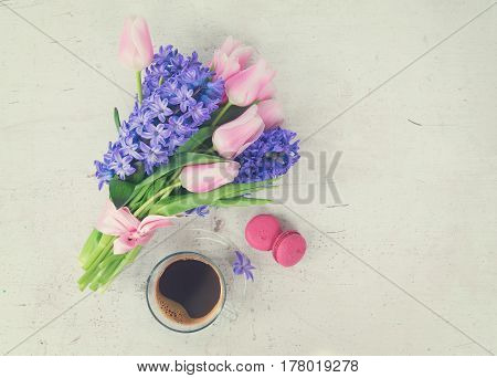 Pink tulips and blue hyacinths flowers with cup of coffee on white wooden table with copy space, retro toned