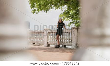 Tourism in Panama City. Young blonde Colombian woman leaning on wall visiting Casco Antiguo as tourist and talking on mobile phone