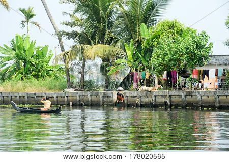Man Rowing A Canoe On The Backwaters Of Alleppey